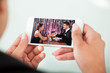 Businesswoman Watching Couple Toasting Wineglasses On Cellphone