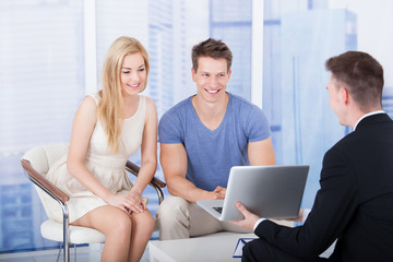 Financial Advisor Explaining Investment Plan To Couple On Laptop