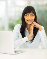young indian office worker sitting in office