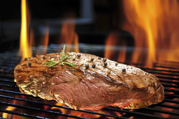 Grilled beef steak on the flaming grill