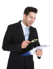 Smiling Businessman Examining Document On Clipboard