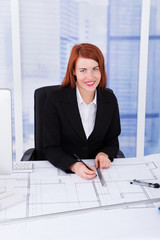 Businesswoman Using Computer With Blueprints At Desk