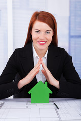 Businesswoman Sheltering Green House Model