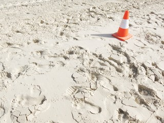 white sand with a traffic cone