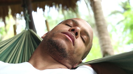 Young man asleep in a hammock swinging in a tropical environment