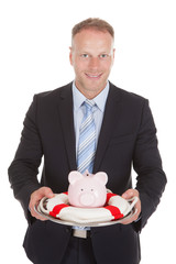 Businessman Protecting Piggybank With Lifebuoy