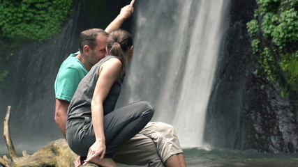 Couple looking at beautiful waterfall in Bali, super slow motion