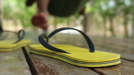Foreground shot of a flip flop as a man swings in a hammock