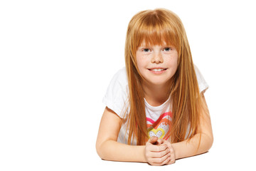 A cheerful little girl with red hair is lying