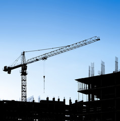 Silhouettes of a construction crane and building on a background