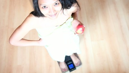woman with apple stepping on bathroom scales