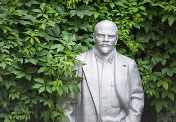Old statue of Lenin looks out from the bushes