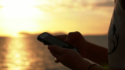 Close up of Woman Hands Using Cell Phone at Sunset. Slow Motion.