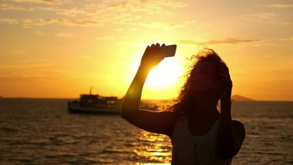 Girl Taking Picture with Smart Phone against Sunset and Sailing