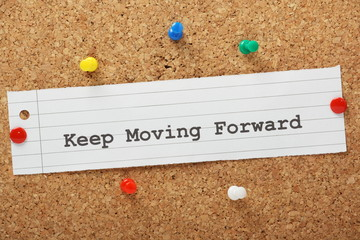 The phrase Keep Moving Forward on a cork notice board