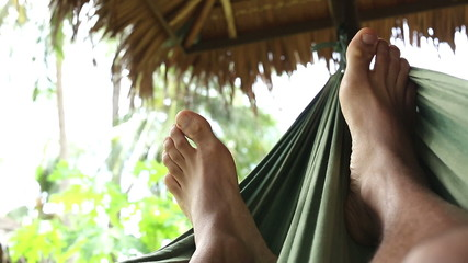 Feet of a man resting in a swinging hammock
