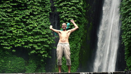 Crazy, excited funny man by amazing waterfall, super slow motion