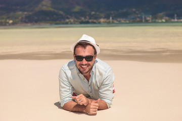 happy young casual man lying on a white sand  beach