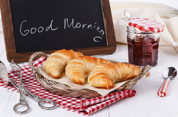 Breakfast with croissants and jam over white wooden background