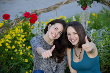 Two beautiful young women giving thumbs up sign and smiling