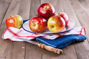 Red apples in a metal plate on a wooden background
