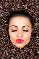 beautiful woman face with closed eyes in the coffee beans