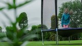Little girl jumps  on trampoline in the summer garden.dolly shot poster