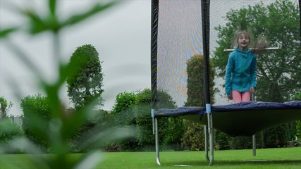 Little girl jumps  on trampoline in the summer garden.dolly shot