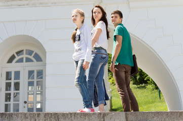 Three young people posing on a wall