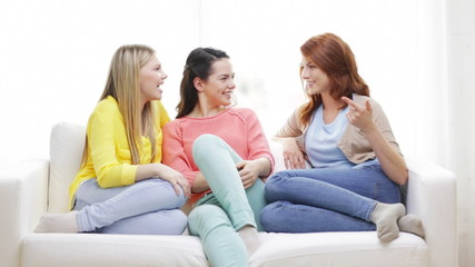 three smiling girlfriends having a talk at home