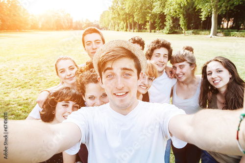 Leinwanddruck Bild Dieci amici si fanno un selfie al parco
