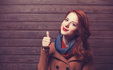 Redhead girl in coat on wooden background.