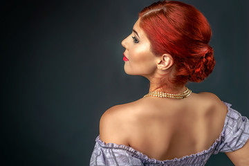 Beautiful redhead with elegant hairstyle and make up