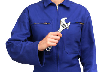 woman in blue work uniform holding a monkey wrench