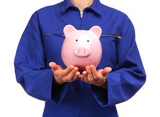 woman in blue work uniform holding a piggy bank
