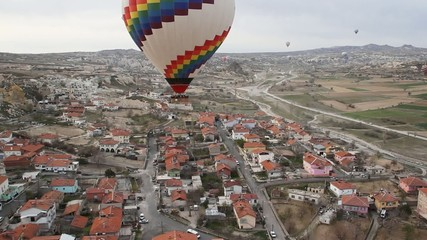 Colorful hot air balloon flying high over a city