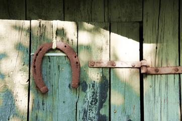 rusty horseshoe hanging on old door
