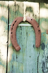 rusty horseshoe hanging on old door
