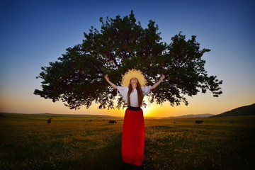 young beautiful woman on field in summer in the sunset light