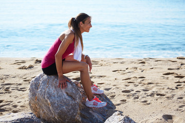 Athletic runner with beautiful figure resting in the beach