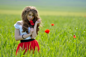 Beautiful girl on blooming poppy field