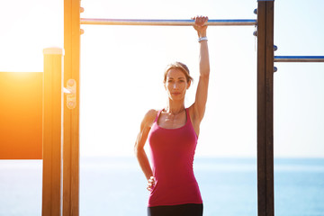 Sporty woman standing at horizontal bar on sea background