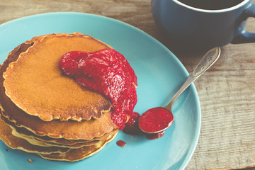 stack of pancakes on a blue plate with red jam