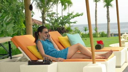 Happy woman talking on cellphone lying on sunbed in garden