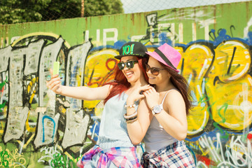Two young girl friends taking a selfie against graffiti wall
