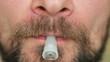 A man with a beard smokes a hookah