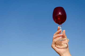 hand hold red wineglass squirm stem on blue sky