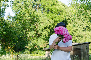 man hiding his face with peony bouquet garden