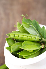 Fresh green peas in bowl on wooden table