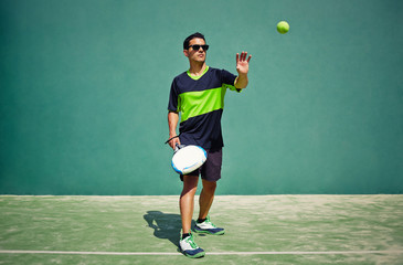 Attractive man with racket in the hands touching the ball